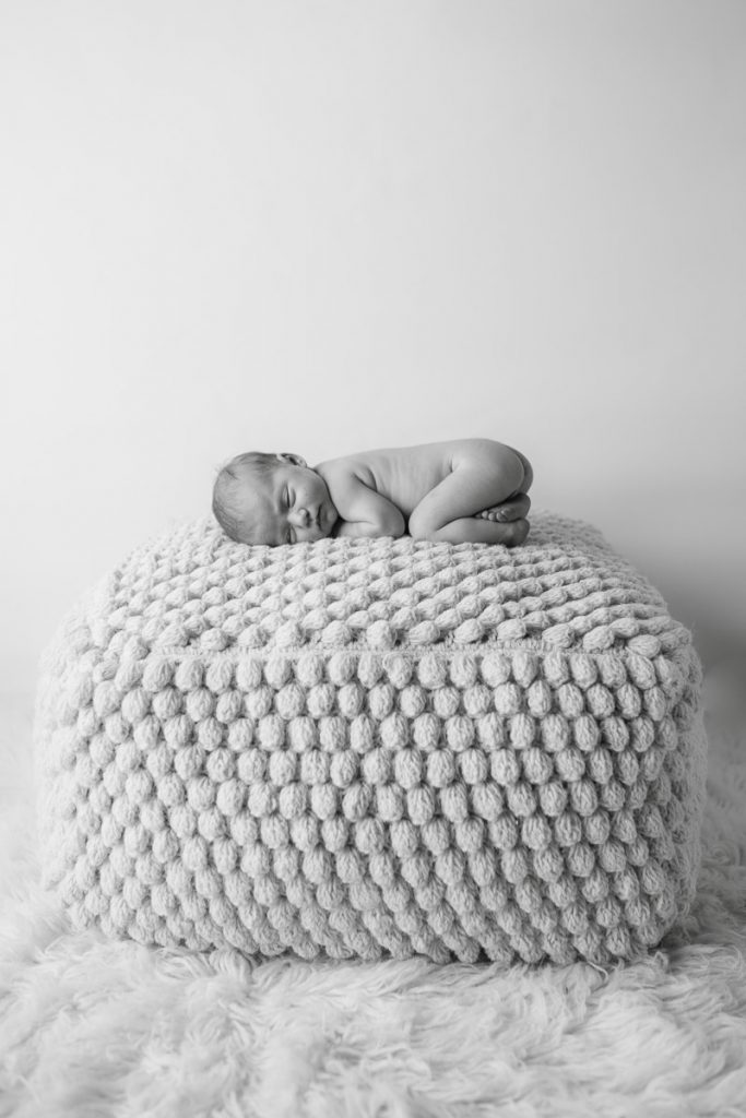 black and white image sleeping newborn on bean bag