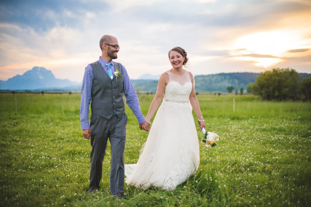 bride and groom walking in field Grand Tetons Wyoming sunet