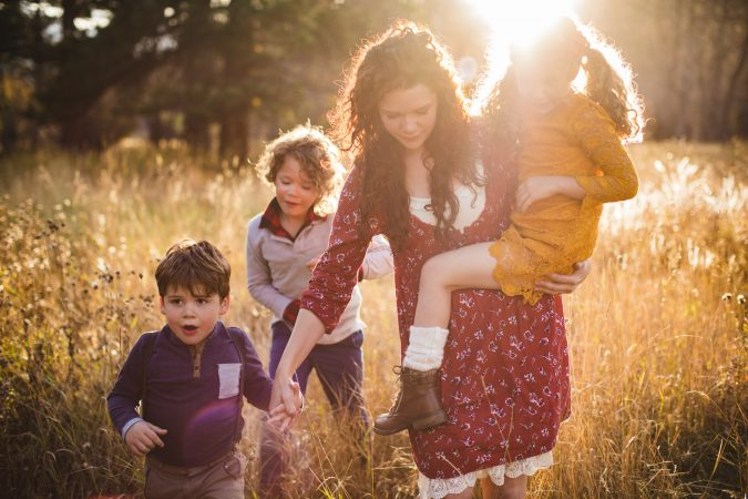 mother and children holding hands golden sunlight dramatic family photograph