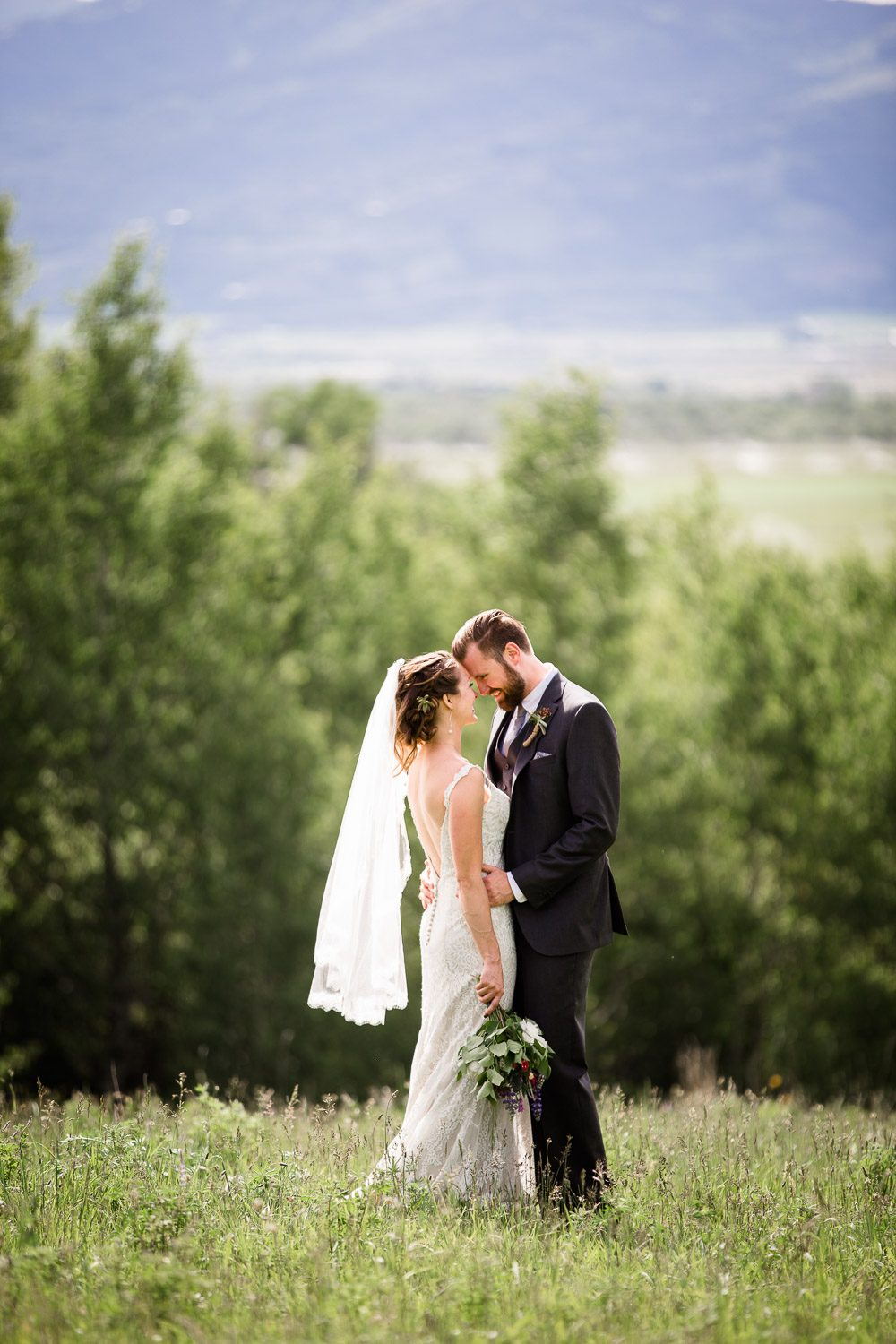 bride and groom in field with sunlight glowing viel
