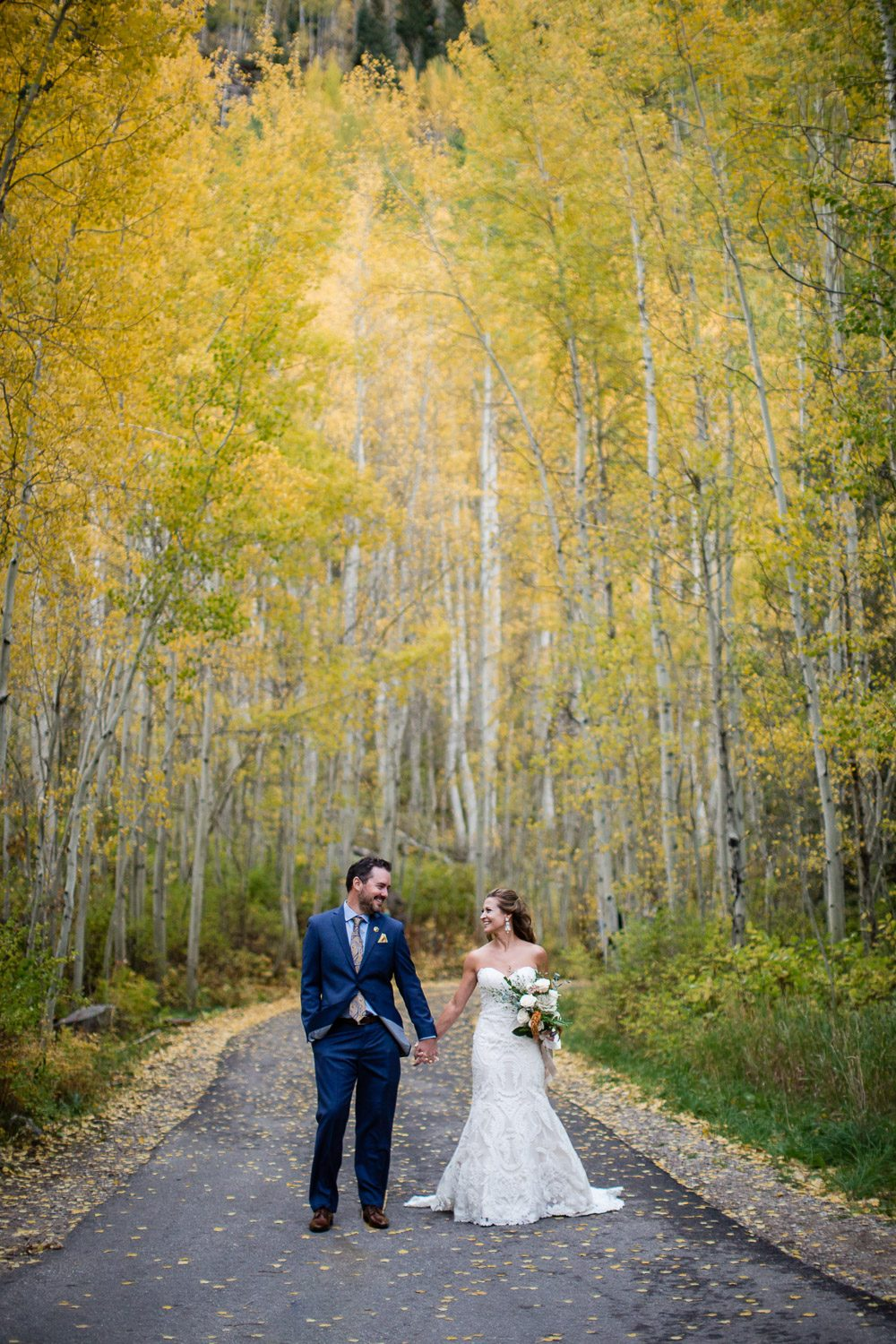 fall Colorado wedding yellow aspens bride and groom holding hands in Vail