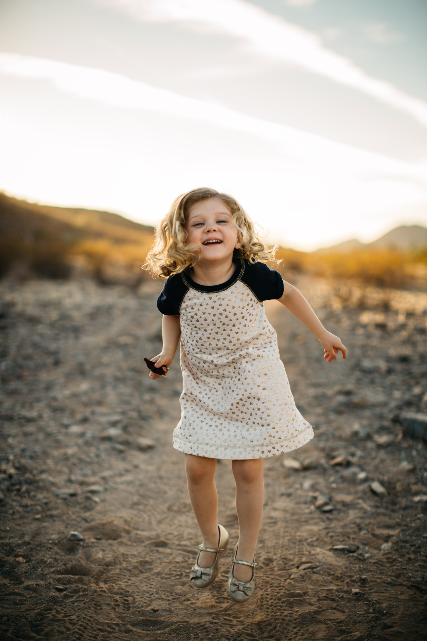 portrait of happy little girl jumping laughing Phoenix Arizona desert mountain location